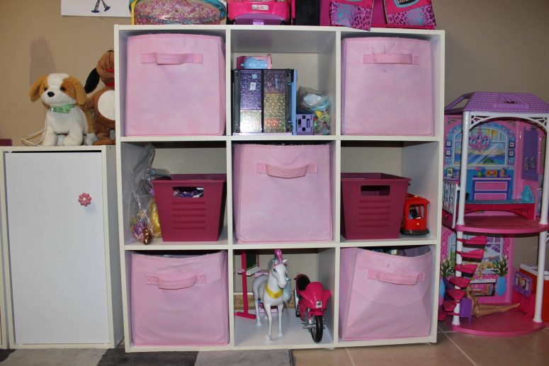 A shelf with baskets in our playroom