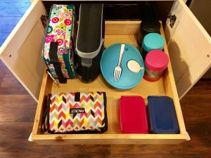 School lunch supplies all in one place in a kitchen cabinet. A back to school routine should be simple so that it alleviates stress instead of adding more!Here are four routine ideas that will work for any family.~Practigal Blog