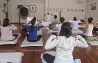 pessoas praticando kundalini yoga em um salão