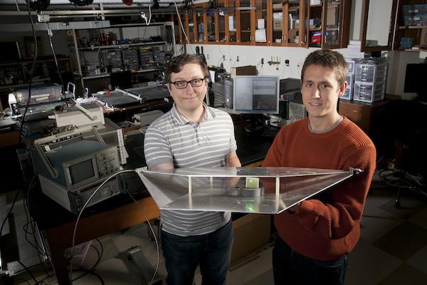 Duke estudiantes de ingeniería Alexander Katko (izquierda) y Hawkes Allen muestran una guía de onda que contiene una sola celda metamaterial power-cosecha, que proporciona energía suficiente para alimentar el LED verde se adjunta.