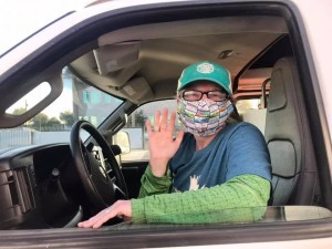 Christina waving from the driver's seat of her van