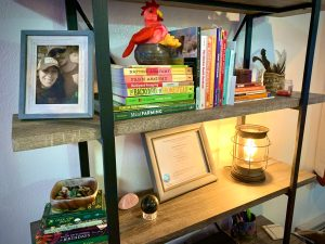 Bookshelf with baskets of rocks, several stacks of books, and a framed photo of Lisa Marie and her husband