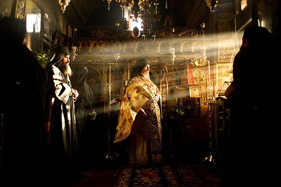 [Picture of hieromonk in light-filled church] Photo: Travis Dove / travisdove.com
