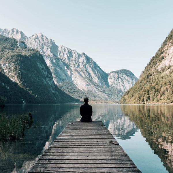 Person sitzt am Steg, Bergsee. Bild für Achtsamkeit