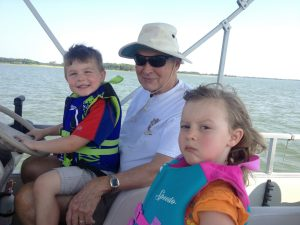 My dad letting his grandkids drive the boat