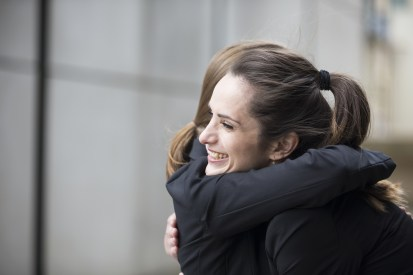 Two Businesswomen hugging each other.