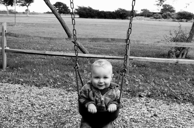 Little Boy happily swinging in B&W landscape