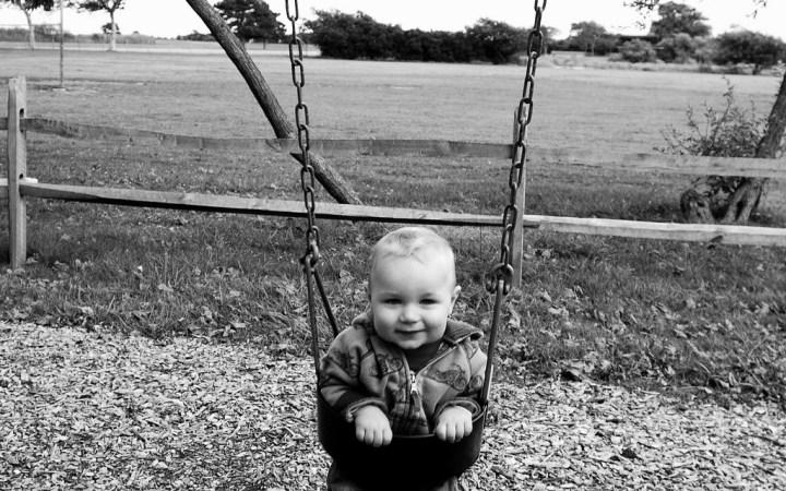 Little Boy happily swinging in B&W landscape