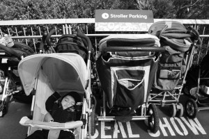 Kid sleeping in stroller near a stroller parking sign