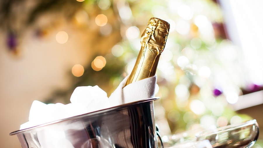 a bottle of chilled champagne in an ice bucket and napkin closeup on lights background