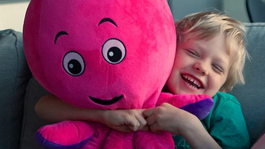 Young boy hugging fluffy Octopus toy