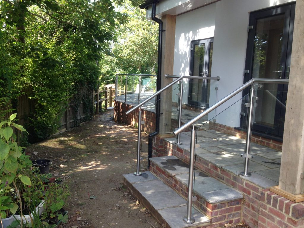 Post and rail glass balustrade to garden