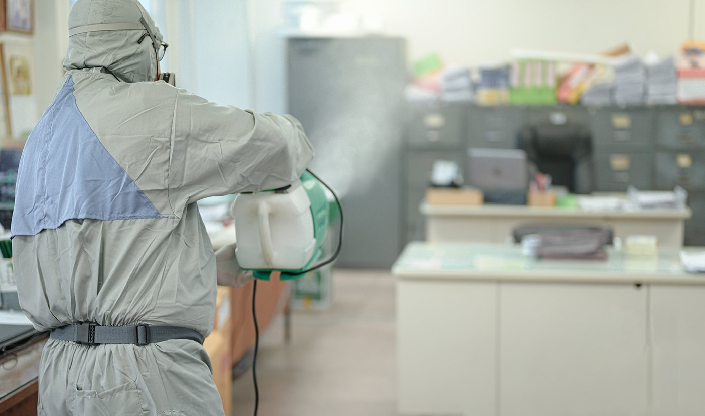 Disinfecting of office to prevent COVID-19, person in white hazm