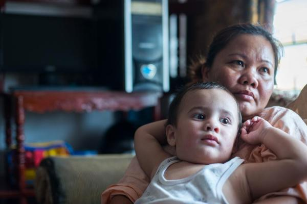 CREDIT: Dave Tacon/Al Jazeera Robert, 18 months, watches television with his mother, Mylene, 37. Mylene used to recruit girls from Manila for work in Angles City's red light district and met Robert's father, a US citizen, while at Owl's Nest, a Go-Go bar on Fields Avenue. After a 20-month relationship with the 55-year-old, a three-time divorcee who lives in the Philippines on a tourist visa, he left Mylene for another woman. Although the father signed Robert's birth certificate his new girlfriend convinced him not to get his son a US passport. He occasionally sends money to Mylene and his son.