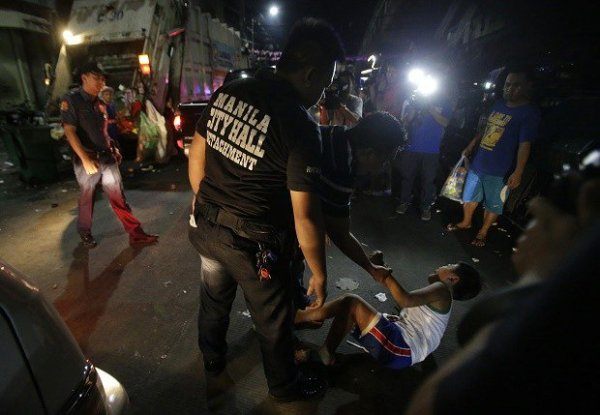 "In this Wednesday June 8, 2016 photo, a Filipino boys cries as he is apprehended by a social worker and police for violating a night to dawn curfew for minors in Manila, Philippines. In a crackdown, dubbed ""Oplan Rody,"" bearing Duterte's name, police rounded up hundreds of children or their parents to enforce a night curfew for minors, and taken away drunk and shirtless men roaming metropolitan Manila's slums. The poor, who were among Duterte's strongest supporters, are getting a foretaste of the war against crime he has vowed to wage. AP"