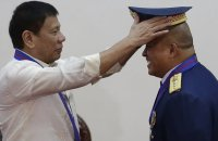Philippine President Rodrigo Duterte places a hat on the head of police Ronald Dela Rosa during a ceremony in Manila. Photograph: Aaron Favila/AP