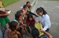 """A volunteer teaches young street children to read and write during a weekend activity of the Catholic youth group """"Do Life Big"""" in the southern Philippine city of General Santos. (Photo by Bong Sarmiento)"""