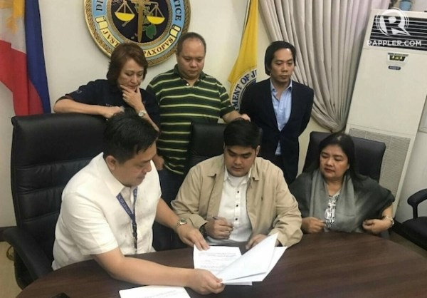 STATE WITNESS. Mark Ventura (middle) signs the document on his admission into the Witness Protection Program in connection with the case of hazing victim Horacio Castillo III. Photo courtesy of DOJ