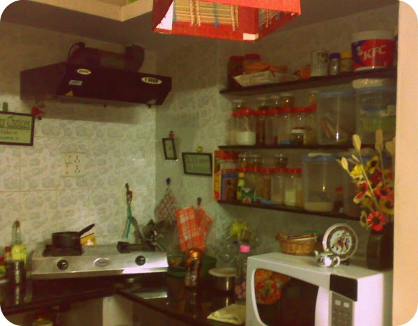 A simple granite top kitchen, with shelves for storage.