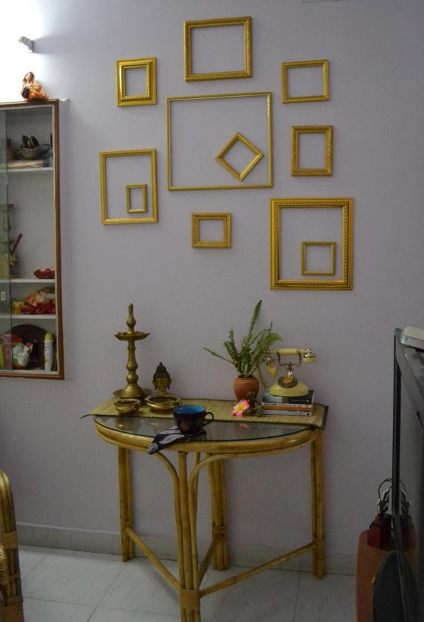 A set of gold picture frames without pictures, placed on the wall.