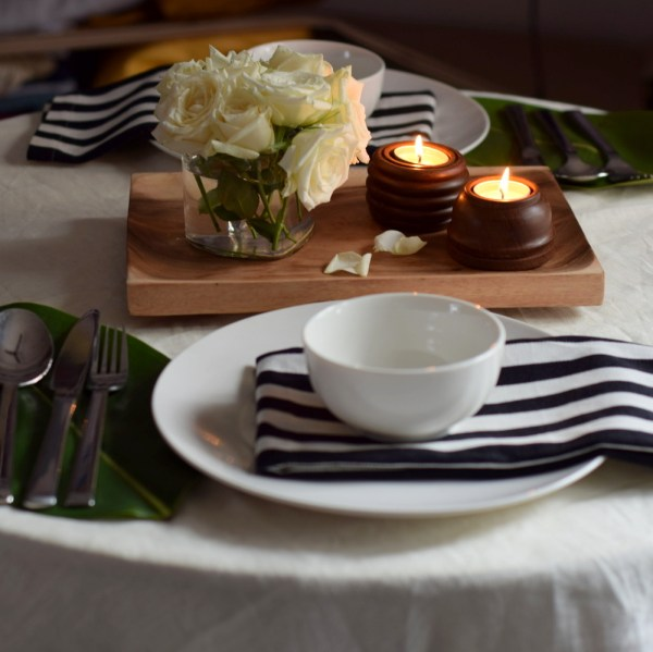 A Mostly monochromatic color scheme table for two. White crockery, back and white striped napkins and some warm wood candles for a cozy dinner.