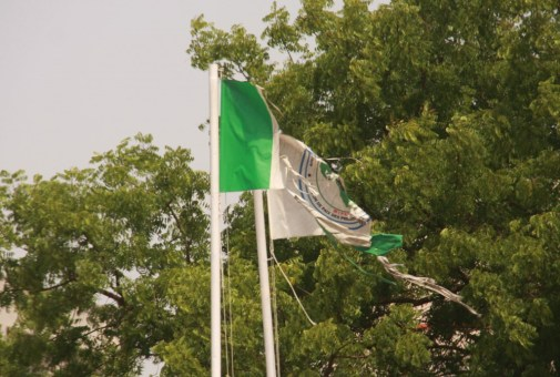 Tattered Nigerian national and African First Ladies' Mission flags flying side by side in front of Bayelsa State House, near Federal High Court, Abuja on Monday