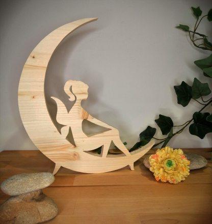 Fée assise sur la lune en bois