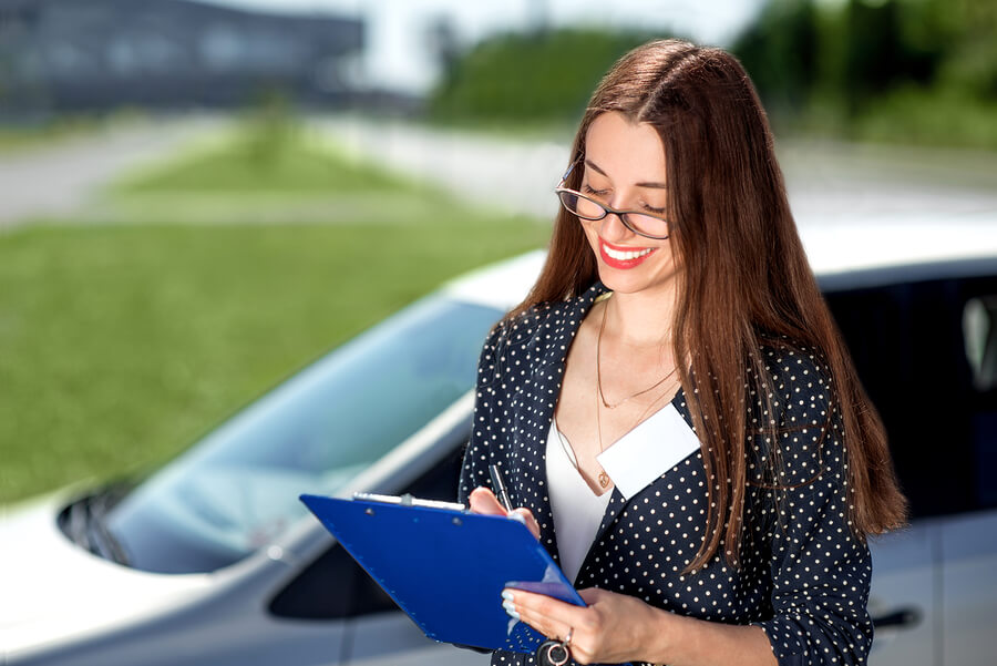 Young woman car rental inspector filling contract