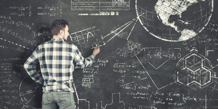 Teenager tries to solve problems on blackboard