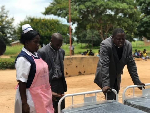 CCAP Synod of Zambia Moderator, Abel Banda (Right) prays over the new beds with Mrs. Banda, Nurse/Midwife at Ndaiwala Rural Health Center, and Rev. Sevatt Kabaghe, CCAP Zambia General Secretary.