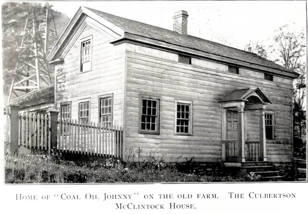 "black and white image from a vintage postcard shows a plain one and a half story house with the caption ""Home of Coal Oil Johnny on the Old Farm."""