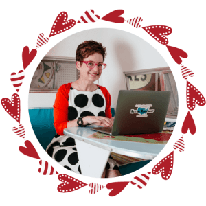 Beth Lennon sits in a vintage trailer, wearing a white dress with big black polka dots and a red sweater. Her laptop is open in front of her so she can share all her insights.