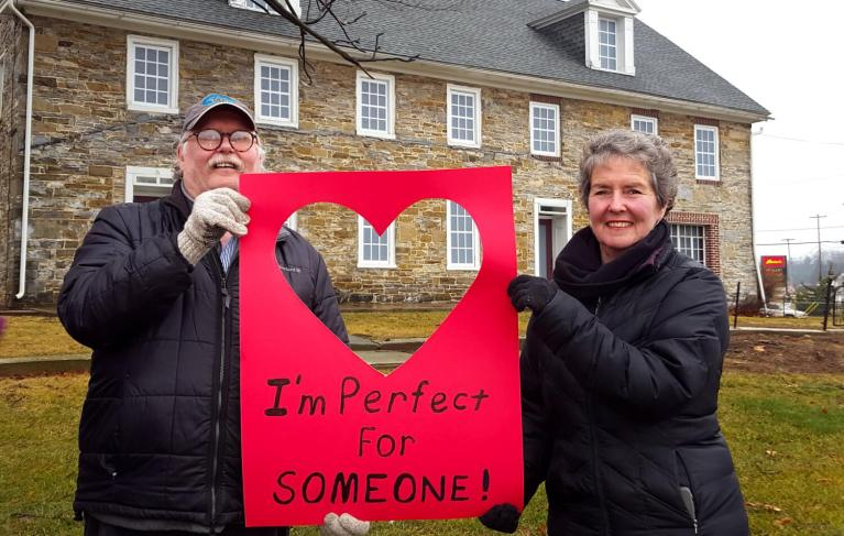 "Two people stand in front of an old stone building holding a valentine that says ""I'm perfect for someone!"""