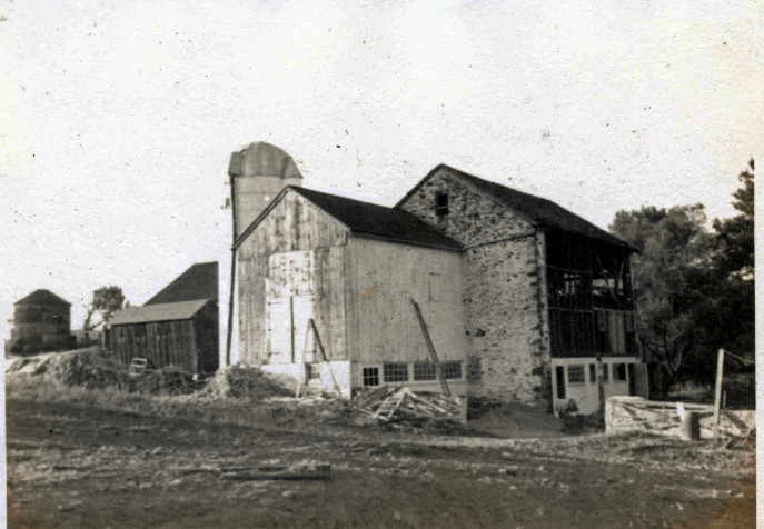 b & w photo of barn buildings and silo with work in progress