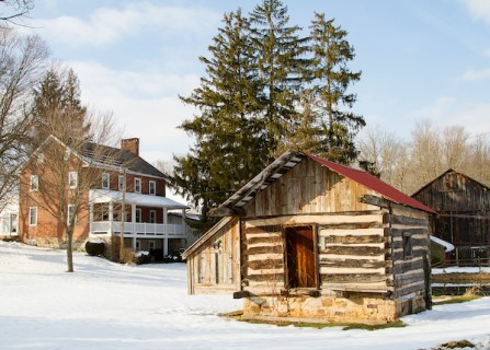 In the foreground, a log buliding. Up the snowy slope behind it, tall pine trees shelter an old brick farmhouse with a porch across the entire first floor front.