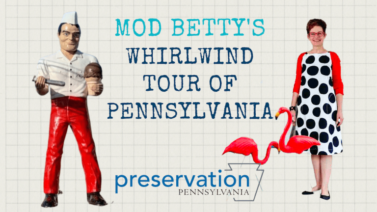 Mod Betty, wearing a red sweater over a black and white polka dot dress, stands with two pink flamingos