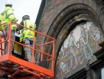 Experts examine the mosaics at the AI Welders building
