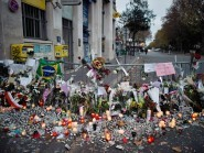 Floweres, candles and tributes cover the pavement near the scene of Friday's Bataclan Theatre terrorist attack