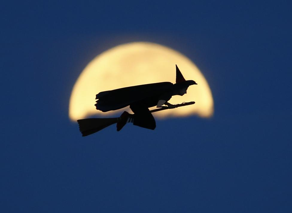 A radio-controlled flying witch makes a test flight past a moon setting into clouds along the pacific ocean in Carlsbad