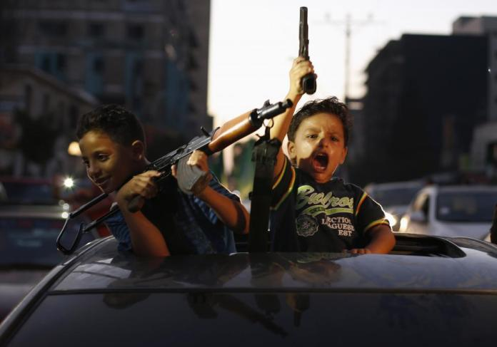 Palestinian children hold guns as they celebrate with others what they said was a victory over Israel, following a ceasefire in Gaza City