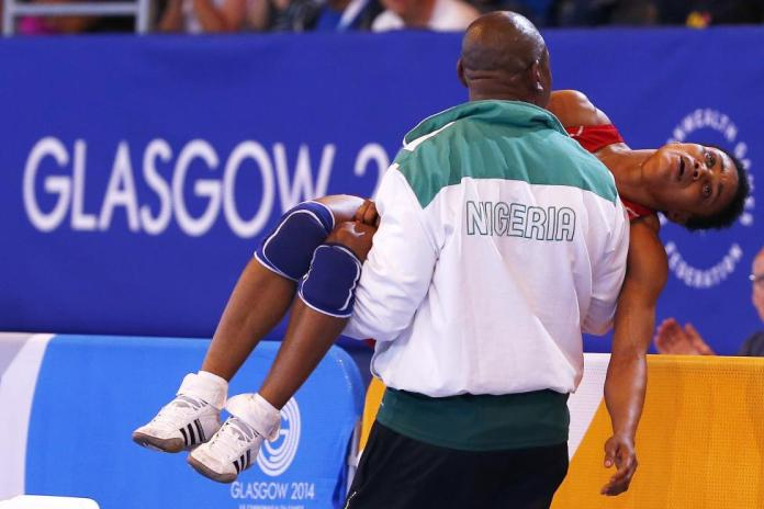 Nwoye of Nigeria is carried away by her coach after she lost her women's freestyle 55kg wrestling semi-final to Laverdure of Canada at the 2014 Commonwealth Games in Glasgow, Scotland