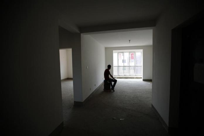 Zhiliang, whose fiancee was onboard Malaysia Airlines Flight MH370 which disappeared on March 8, 2014, is silhouetted at an empty house which he had planned to decorate with her for their marriage, in Tianjin