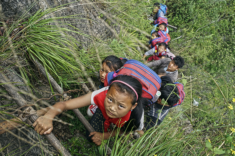 Wearing their school backpacks, children climb up a bamboo ladder on their way home from school.