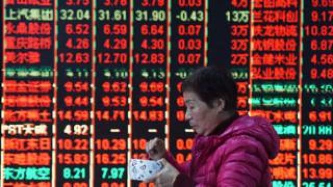 A woman walks past stock market board in China