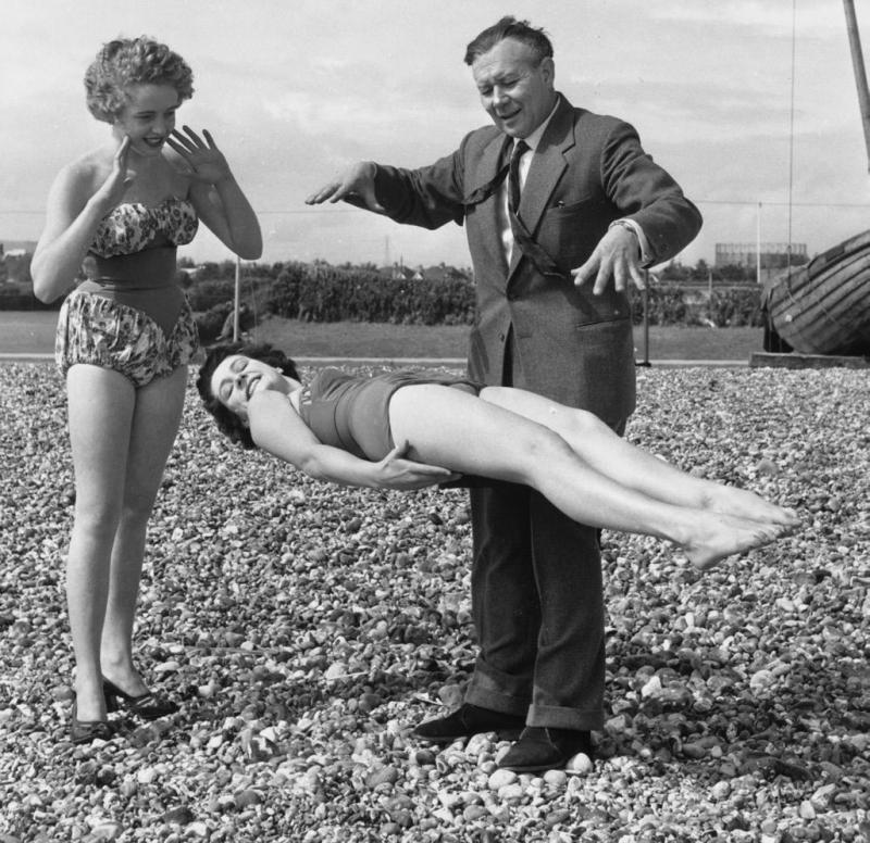 Magician Robert Harbin demonstrates one of his levitation tricks to a couple of sunbathers on the beach at Eastbourne.