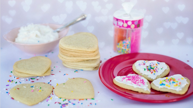 heart shaped sugar cookies topped with icing and confetti candy
