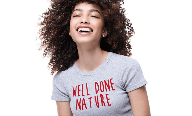 woman with curls wearing a white tshirt with the words well done nature