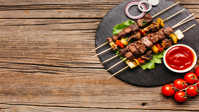 braai and vegetable skewers on a flat black plate on a wooden table