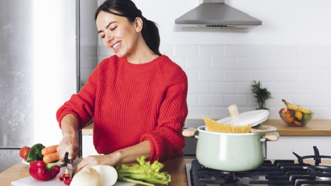 woman in red jersey cutting up vegetables on a kitchen counter to make soup