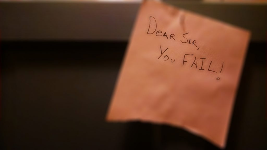 "A sign nailed to a door reading ""Dear Sir: You Fail!"""